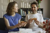 Happy couple sitting on sofa and eating pizza at home — Stock Photo