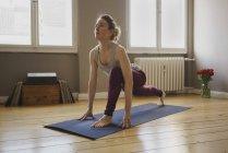 Femme qui s'étend sur tapis d'exercice à la maison — Photo de stock
