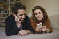 Улыбающаяся женщина показывает смартфон мужчине, когда лежит на кровати дома — стоковое фото