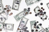 Однодолларовые купюры и монеты на белом фоне — стоковое фото