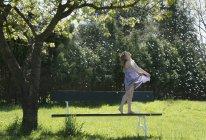 Garota despreocupada no banco sob a árvore de primavera com queda Floradas de primavera — Fotografia de Stock