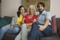Portrait senior mother sitting with daughter and son on living room sofa — Stock Photo