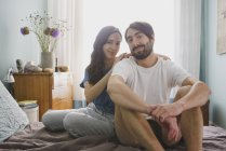 Portrait smiling couple relaxing on bed — Stock Photo