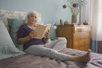 Senior woman reading book on bed — Stock Photo