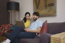 Coppia utilizzando laptop sul divano del soggiorno — Foto stock
