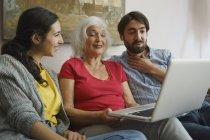 Mère aînée utilisant un ordinateur portable avec sa fille et son fils sur le canapé du salon — Photo de stock