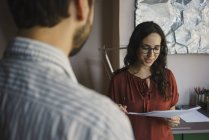 Businesswoman discussing paperwork with colleague in office — Stock Photo