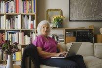 Retrato confiado mujer mayor utilizando el ordenador portátil en el sofá de la sala - foto de stock