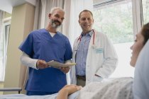 Doctors making rounds, talking with patient in hospital room — Stock Photo