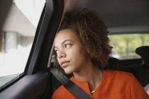 Ragazza premurosa che guida in macchina, guardando fuori dal finestrino — Foto stock