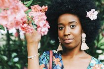 Ritratto giovane donna sicura di sé con fiore rosa nei capelli — Foto stock