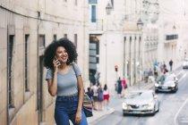 Jovem sorridente a falar ao telefone inteligente na rua urbana, Lisboa, Portugal — Fotografia de Stock