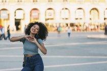 Jeune enthousiaste portrait formant en forme de cœur avec les mains à Praça do Comercio, Lisbonne — Photo de stock