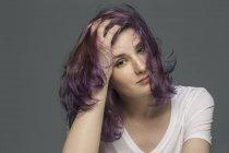 Porträt von eine selbstbewusste junge Frau mit gefärbten und zerzausten Haaren vor grauem Hintergrund — Stockfoto