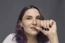 Retrato de una mujer joven con el pelo teñido mordiendo uñas contra fondo gris - foto de stock