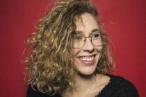 Portrait de femme souriante aux cheveux bouclés et portant des lunettes sur fond rouge — Photo de stock
