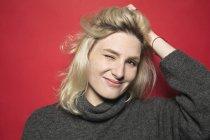 Ritratto di donna sorridente e ammiccante con mano sulla testa sullo sfondo rosso — Foto stock
