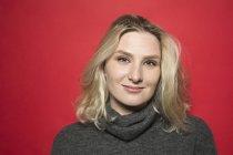 Портрет женщины с светлыми волосами, улыбающейся и в сером свитере с водолазкой — стоковое фото