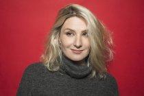 Portrait d'une femme aux cheveux blonds souriant et porter le chandail à col roulé gris — Photo de stock