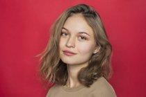 Portrait de femme avec des cheveux châtain clair et souriant sur fond rouge — Photo de stock