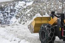 Tracteur labourant la neige au bord de la route — Photo de stock