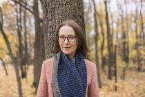 Ritratto donna fiduciosa in sciarpa in piedi contro l'albero nel parco autunnale — Foto stock