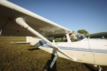 Father and son in small airplane in sunny field — Photo de stock