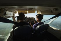 Father and son flying small airplane — Stock Photo
