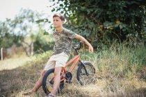 Мальчик с велосипедом в траве — стоковое фото
