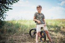 Портрет впевнений хлопчик на велосипеді в сільській місцевості — стокове фото