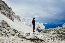 Teenage boy standing on rock overlooking rugged mountains, Drei Zinnen Nature Park, South Tyrol — Stock Photo