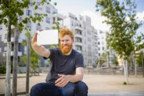 Улыбающийся мужчина с бородой делает селфи с цифровым планшетом в городе — стоковое фото