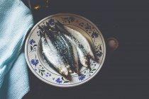 Bodegón fresco salado, sardinas enteras en plato - foto de stock