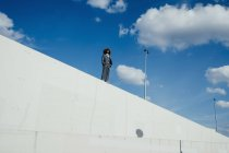 Cool, well-dressed young man with afro standing on sunny urban wall — Stock Photo