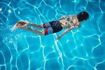 Boy swimming in blue swimming pool — Stock Photo