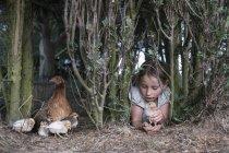 Fille exploitation bébé poussin sous l'arbre à la ferme — Photo de stock