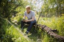 Man with beard using digital tablet in sunny garden — Stock Photo