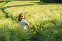 Portrait smiling girl in rural, green wheat field — Stock Photo