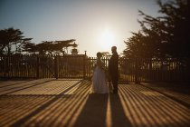 Bride and groom standing outside sunny lighthouse, Monterey, Lucas Point, California, USA — Stock Photo
