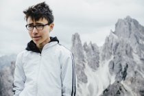 Teenage boy standing at rugged mountain peaks, Drei Zinnen Nature Park, South Tyrol, Italy — Stock Photo