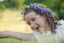 Happy, carefree girl with flowers in hair — Stock Photo