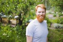 Porträt lächelnder, selbstbewusster Mann mit roten Haaren im Garten — Stockfoto