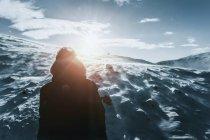 Підлітковий хлопчик, що стоїть на сонячній, засніженій горі, Рейкягалур, Ісландія — стокове фото