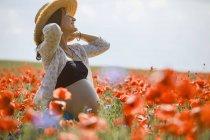 Беззаботная беременная женщина на солнечном идиллическом сельском маковом поле — стоковое фото