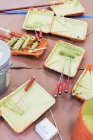 Green paint, paint rollers and trays — Stock Photo