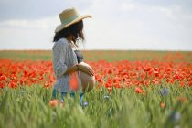 Pregnant woman standing in sunny, idyllic rural field with red poppies — Stock Photo