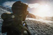 Teenager steht auf einem sonnigen, schneebedeckten Berg, reykjadalur, Island — Stockfoto