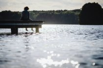 Женщина отдыхает на берегу солнечного озера — стоковое фото