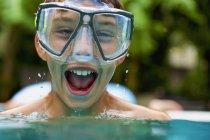 Portrait exuberant boy in swimming goggles swimming — Stock Photo