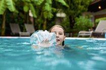 Portrait of smiling girl swimming, splashing hand in swimming pool — Stock Photo